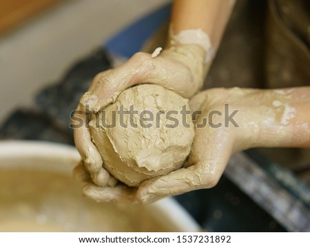 Photography of the Potter's Wheel and human hands with clay ball preparing for crafting work. Concepts of handicraft. Arts school. View from above / top view. #1537231892