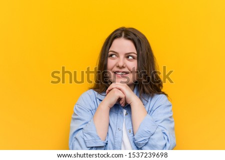 Young curvy plus size woman keeps hands under chin, is looking happily aside. #1537239698