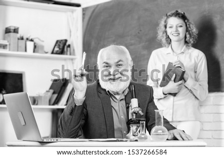 Biological research. Teacher and girl with notepad near chalkboard. College university education. Biologist or chemist with microscope teaching student biology. Biology science. Study biology. #1537266584