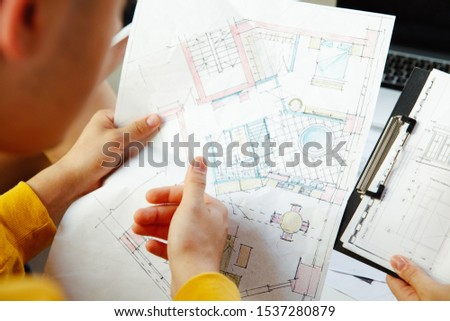 Interior designer working with young couple. Lovely family and professional designer or architector discussing conept of future interior, working with colour palette, room drawings in modern office. #1537280879