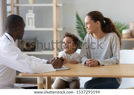 Happy young mom and little preschooler son visiting african American male family doctor consult on health problems, smiling mother and boy child talk with positive pediatrician in hospital or clinic #1537293194
