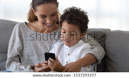 Loving young mom relax enjoy weekend time with little biracial son playing on smartphone together, caring happy mother have fun rest with small boy child using cellphone watch cartoon online