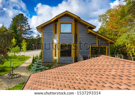 View cottage village in the summer. Rent cottages. Family vacation in nature. Rest in a country house. Landscape design. Roofs of houses with brown soft tiles. #1537293314