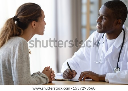 Smiling african American male doctor listen to young woman complains make notes in client medical card, biracial man general practitioner consulting millennial female patient writing prescription #1537293560