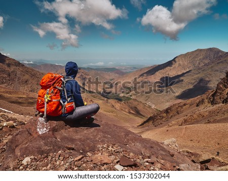 Tourist girl on the hike sitting on the rock in High Atlas mountains and enjoying the magnificient view of the valley near Imlil in Morocco, Africa Royalty-Free Stock Photo #1537302044
