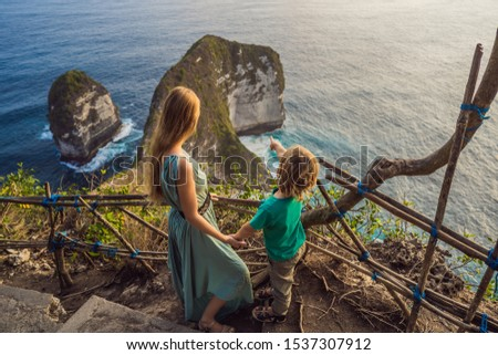 Family vacation lifestyle. Happy mother and son stand at viewpoint. Look at beautiful beach under high cliff. Travel destination in Bali. Popular place to visit on Nusa Penida island #1537307912