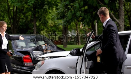 Young woman looking at drunk male driver with beer bottle near crushed cars #1537347923