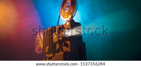 Vintage old fashioned projector in a dark room projecting a film, cinematography concept