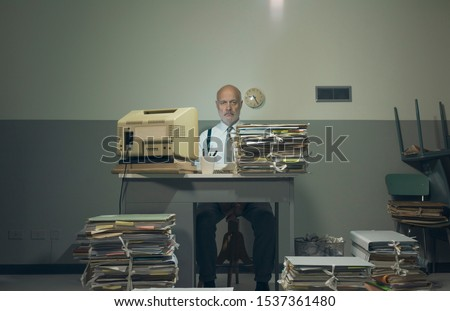 Frustrated vintage style businessman working in a rundown old office space, he is overloaded with papework #1537361480