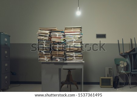 Piles of paperwork and files on a small desk in a rundown messy office space with cheap furniture, taxes and overwork concept #1537361495