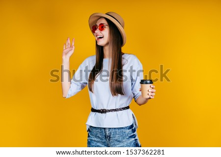 the girl in the hat and glasses makes a welcome sign with her hand, smiles broadly and holds coffee in her hand. Studio color yellow #1537362281
