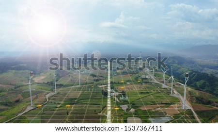 Aerial view of windmills with digitally generated holographic display tech data visualization. Wind power turbines generating clean renewable energy for sustainable development in a green ecologic way #1537367411