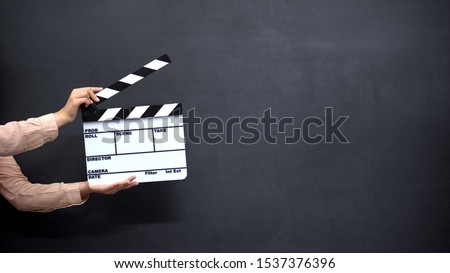 Female hands using clapperboard against black background, shooting movies Royalty-Free Stock Photo #1537376396