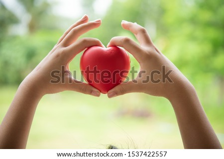 Two hands of child holding a red of rubber heart with green grass background. Showed the coordination, collaboration of business or requires sacrifice, attention, unity, charity, care or love of human #1537422557