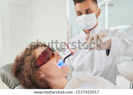 Side view of attractive female patient in protective glasses lying on dental chair with opened mouth while male dentist in white uniform and mask keeping ultraviolet in clinic. Concept of medicine. #1537425017