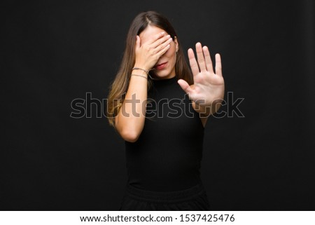 young pretty woman covering face with hand and putting other hand up front to stop camera, refusing photos or pictures against black wall #1537425476