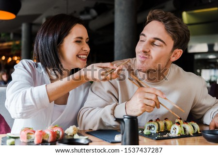 selective focus of happy woman holding chopsticks with tasty sushi near cheerful man in restaurant  #1537437287