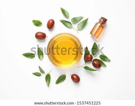 Bowl with jojoba oil and seeds on white background, top view #1537451225