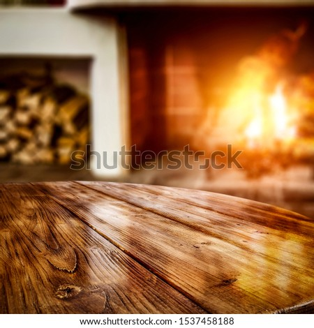 Table background of free space for your product and warm light of fire in fireplace. Home interior and chrsitmas time.