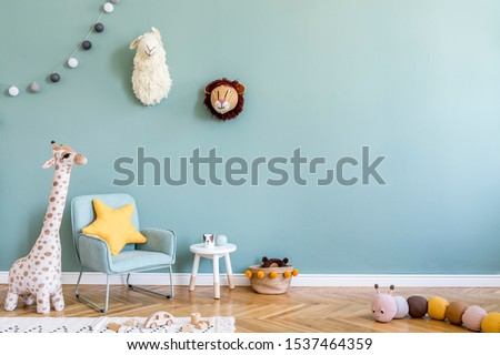Stylish scandinavian kid room with toys, teddy bear, plush animal toys, mint armchair, cotton balls. Modern interior with eucalyptus background walls, Design interior of childroom. Template