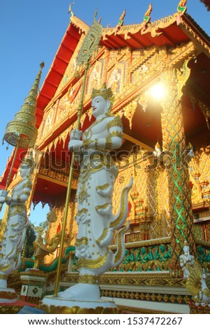 """Statues decorated with statues of statues in front of the golden temple door """"Wat Sri Saeng Thong"""" Ubon Thai. #1537472267"""