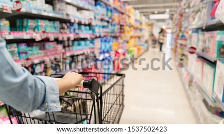 shopping in a supermarket concept.Shopping in supermarket a shopping cart view with motion blur.Close up of a woman shopping in a supermarket.Customer pushing a cart in a supermarket. #1537502423