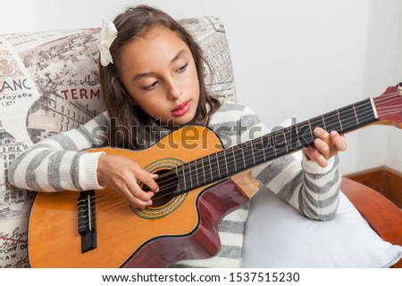 BOGOTA, COLOMBIA – OCTOBER, 2019: Beautiful little girl learning to play the guitar at her home #1537515230