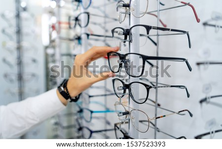 Row of glasses at an opticians. Eyeglasses shop. Stand with glasses in the store of optics. Woman's hand chooses spectacles. Eyesight correction. Royalty-Free Stock Photo #1537523393