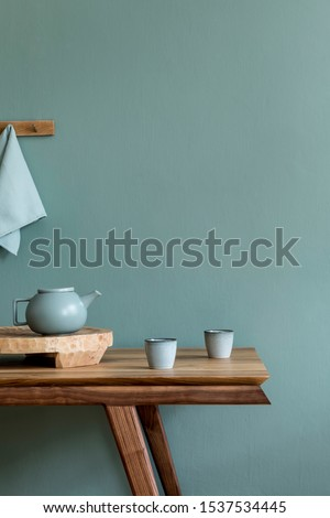 Stylish and minimalistic dining room interior with wooden table, teapot with cups, fruit tray and elegant accessories. Eucalyptus color. Ready to use. Template. Modern home decor. Copy space. #1537534445