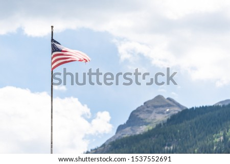 Flagpole on main street in Silverton, Colorado summer with American flag waving in the wind and mountain peak in summer and blue sky clouds #1537552691