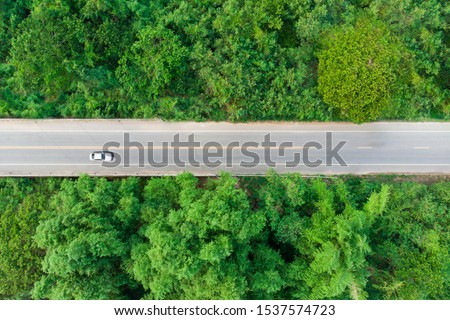 Aerial view of the road passing the forest  with a car passing by #1537574723