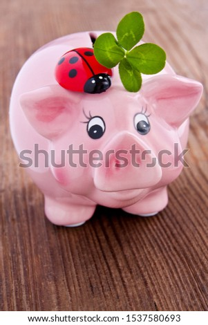 Pink lucky pig with lucky clover on a wooden backgurd #1537580693