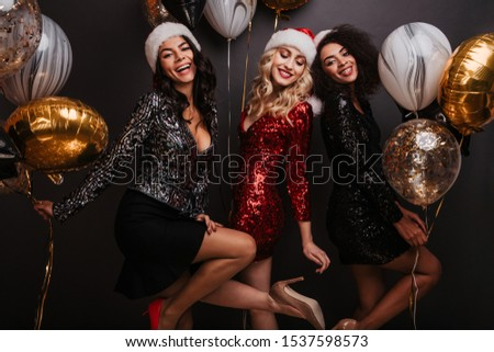 Well-dressed girls having fun at new year party. Studio portrait of international friends celebrating christmas. #1537598573