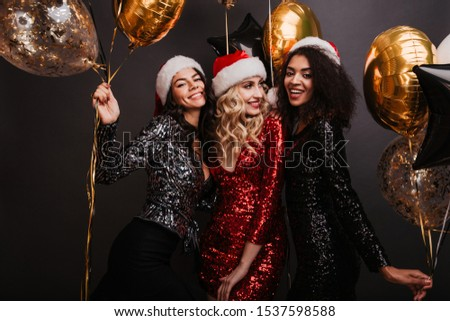 Appealing blonde woman in red dress celebrating winter holidays with friends. Studio shot of girls dancing with balloons. #1537598588
