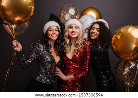 Carefree female friends enjoying christmas time. Studio portrait of company of girls in santa claus hats. #1537598594
