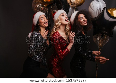 Pretty girls in good mood celebrating winter holidays. Indoor shot of female friends in santa claus hats. #1537598597