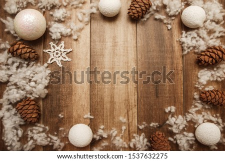 Christmas frame of white balls and fir cones on a wooden background. Space for text #1537632275