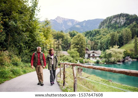 A senior pensioner couple hiking in nature, holding hands. #1537647608