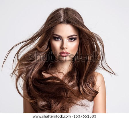 Portrait of a beautiful woman with a long hair. Young  brunette model with  beautiful hair - isolated on white background. Young girl with hair flying in the wind. #1537651583