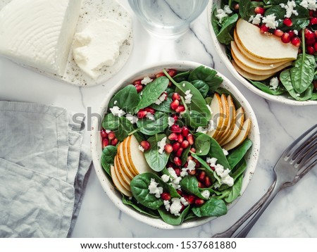 Fresh salad with baby spinach, pear, pomegranate and cottage cheese. Two bowls with delicious summer fruit salad on marble table. Copy space for text. Ideas and recipes for healthy breakfast or lunch #1537681880