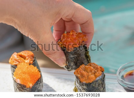 A man's hand placing a piece of sushi on a kind of food chopping board placed on a table. #1537693028