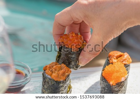 A man's hand placing a piece of sushi on a kind of food chopping board placed on a table. #1537693088