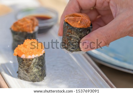 Man who only sees one hand placing a piece of sushi on a kind of food chopping board placed on a table. #1537693091
