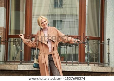 stylish blonde woman walking around a city #1537698374