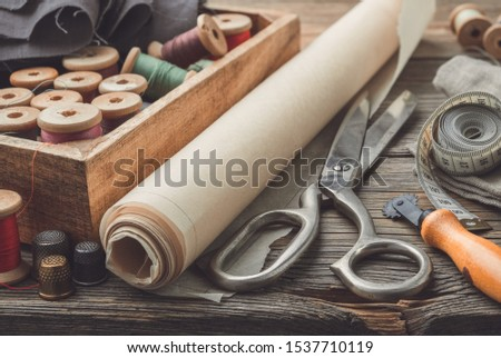 Sewing items: retro tailoring scissors, measuring tape, thimble, vintage spools of thread in wooden box, patterns on paper and tailor cutting knife. #1537710119