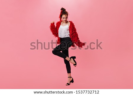 Nice woman in woolen jacket and black pants dancing on pink background #1537732712