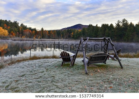 Forest in autumn foliage with mirror reflection in calm lake with mountain backdrop, Adirondacks New York #1537749314