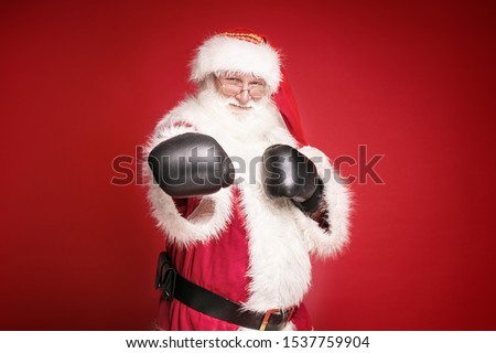 Real Santa Claus in boxing gloves is ready to fight , looking at camera, standing on red studio background. Merry Christmas and Happy New Year concept.  Royalty-Free Stock Photo #1537759904