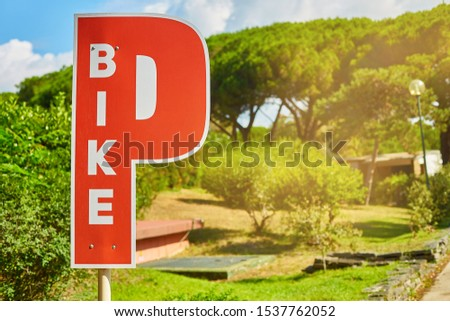 Bicycle Parking sign in the form of the letter P in red on a background of green trees #1537762052