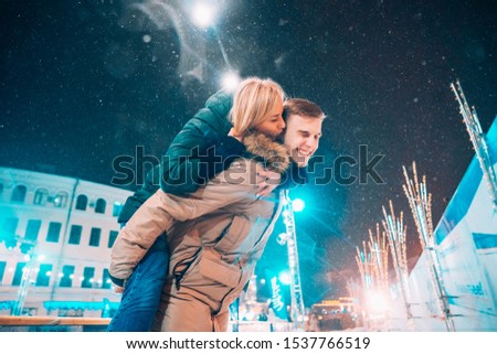 Cheerful and playful couple in warm winter outfits are fooling around #1537766519